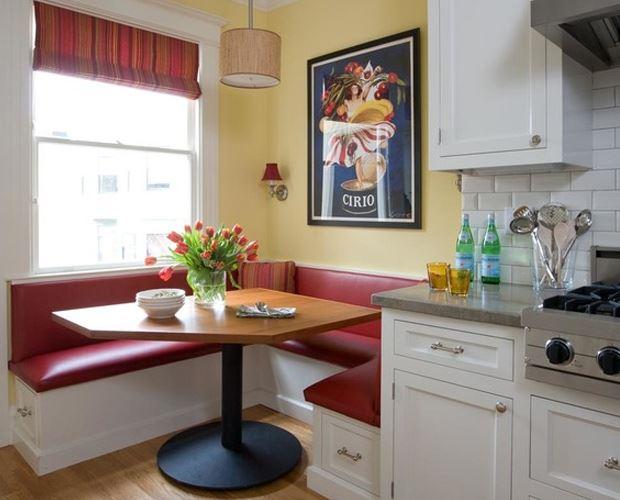 Красный кожаный диванчик в интерьере маленькой кухни