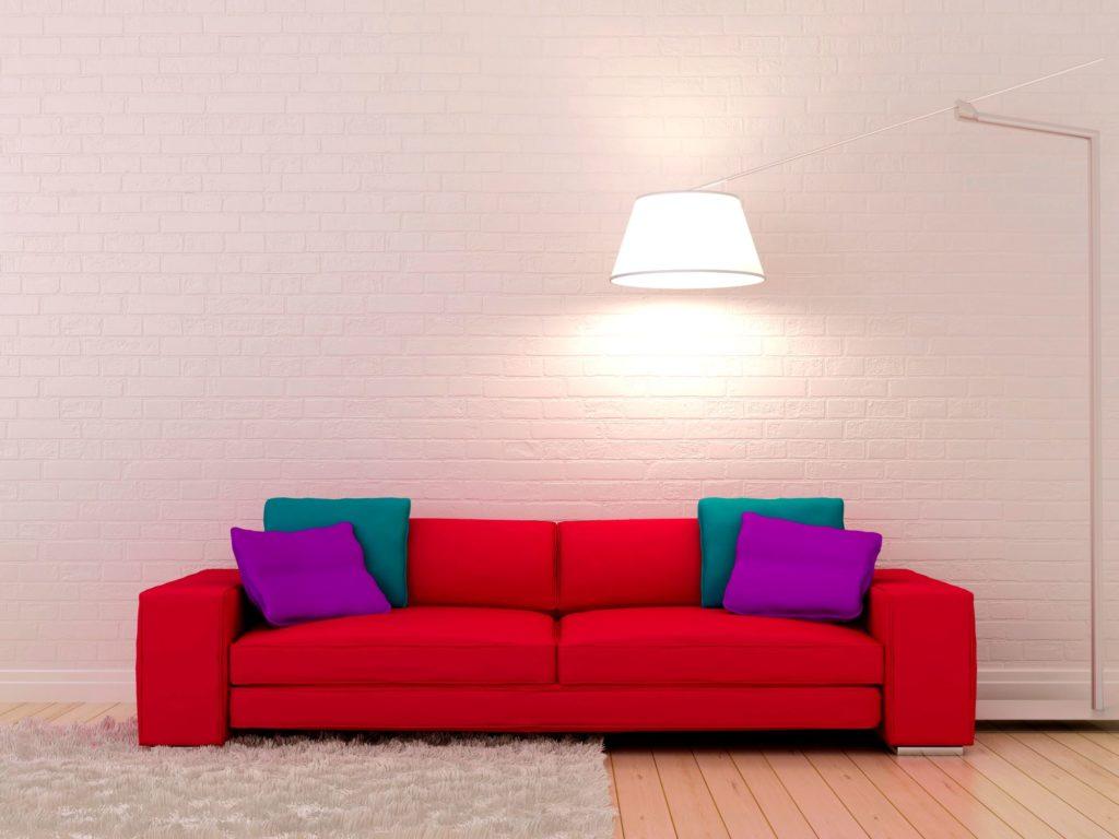 Яркий красный диван у светлой стены под кирпич