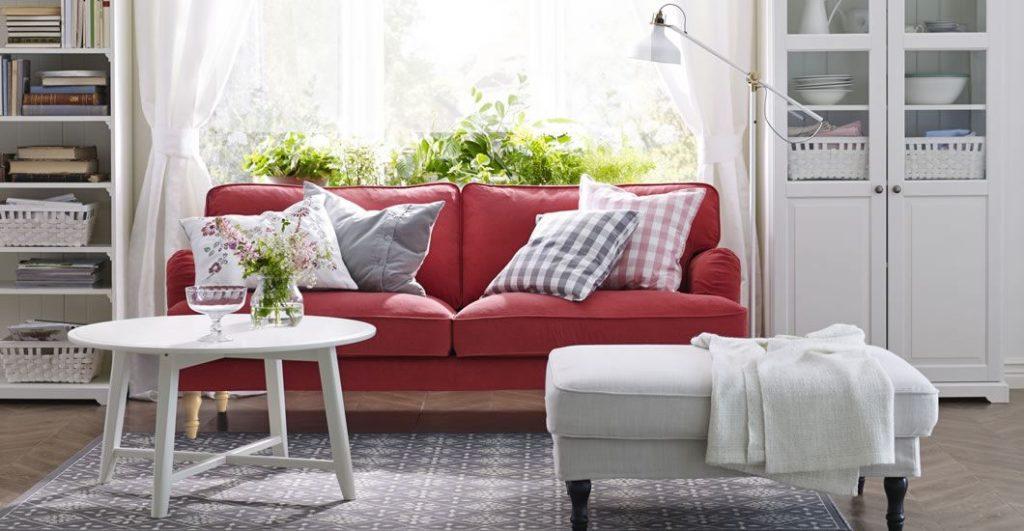 Небольшой прямой красный диван в светлой комнате