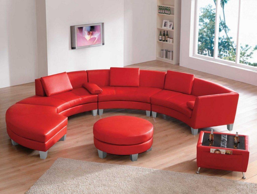 Красный радиусный диван в интерьере с круглым пуфиком