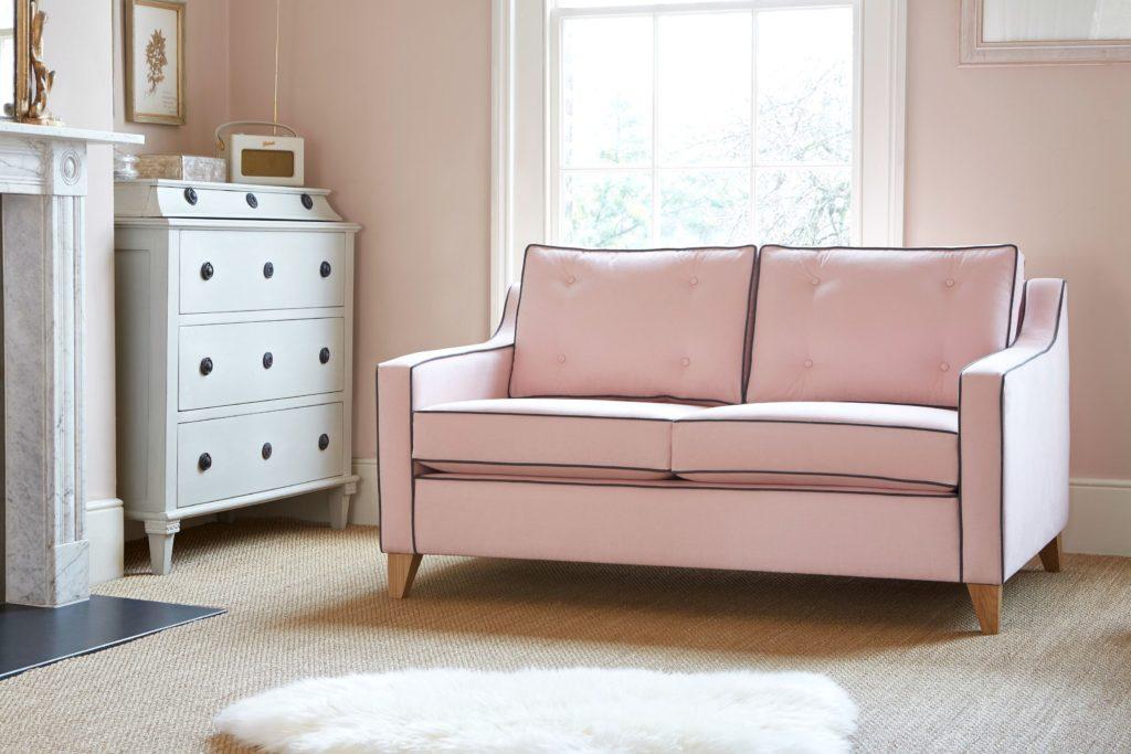 Розовый диван в комнате со стенами розового цвета