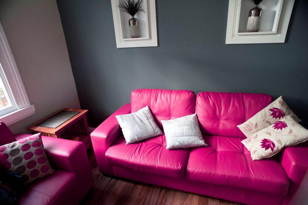 Контрастный кожаный диван розового цвета в интерьере комнаты
