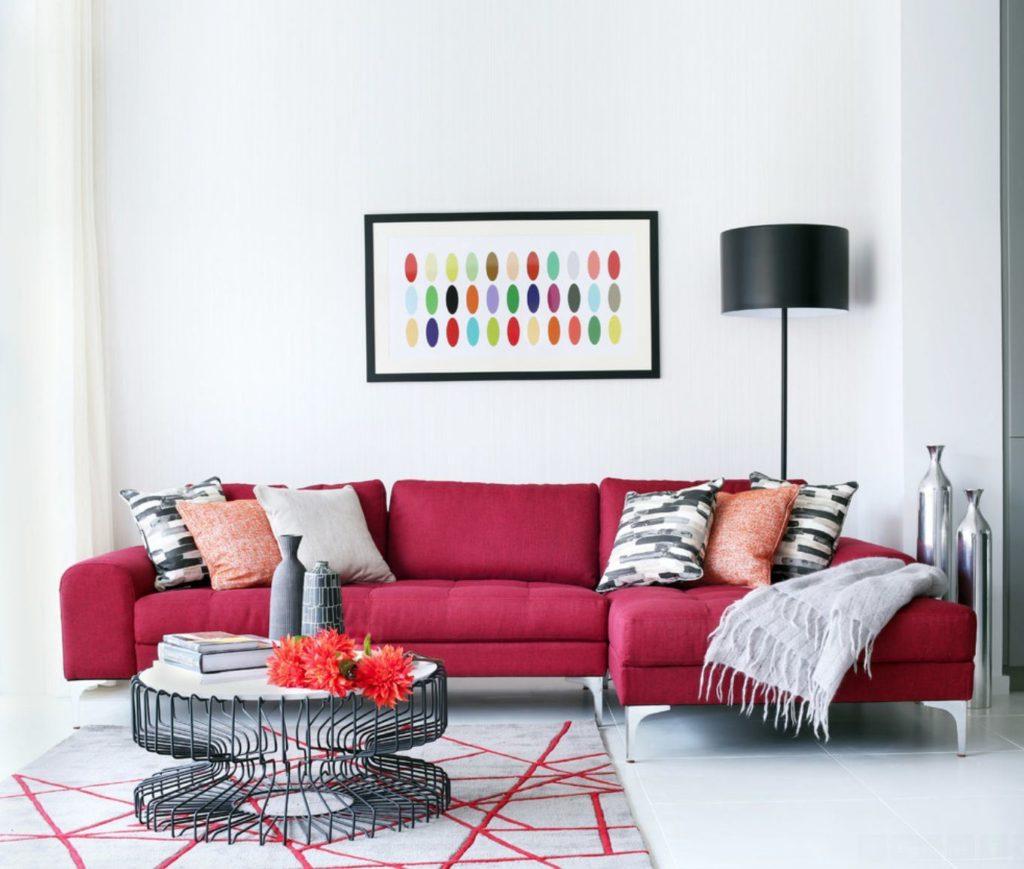 Интерьер комнаты с розовым угловым диваном у стены