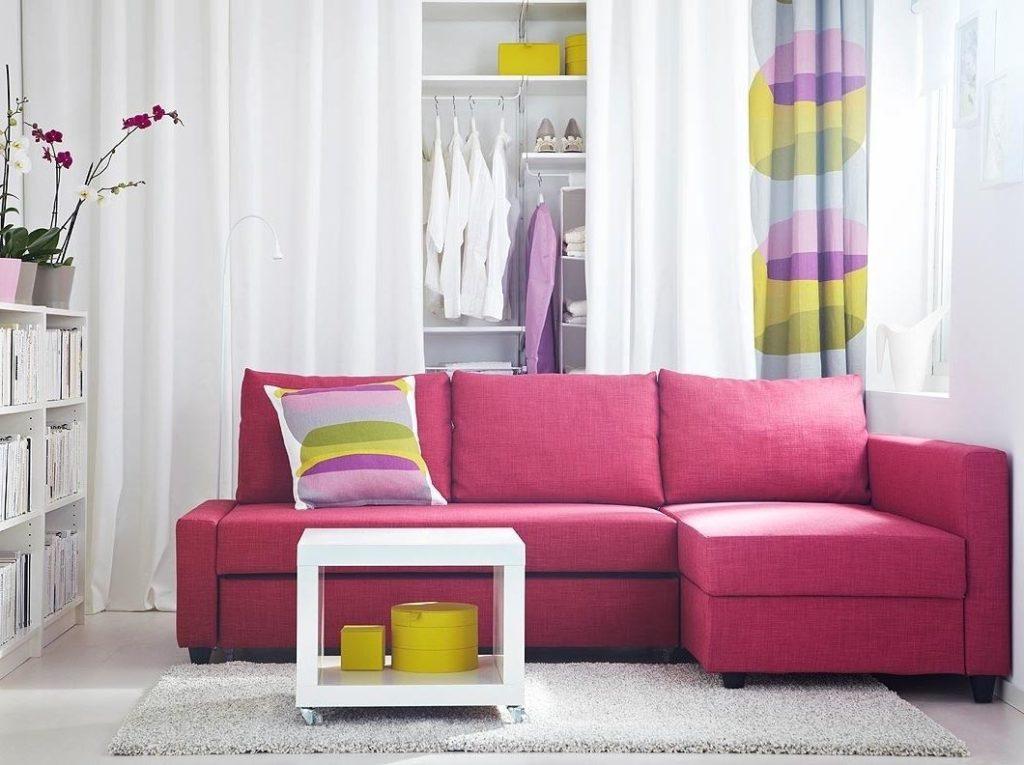 Небольшой угловой диван розового цвета с подушками
