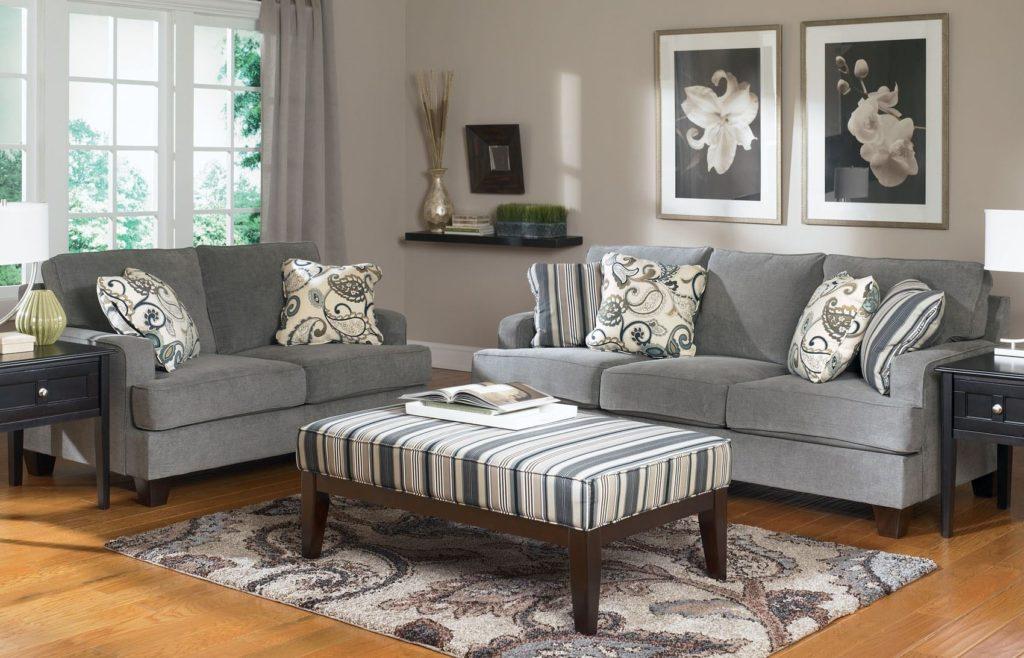 Два небольших серых дивана в интерьере у окна