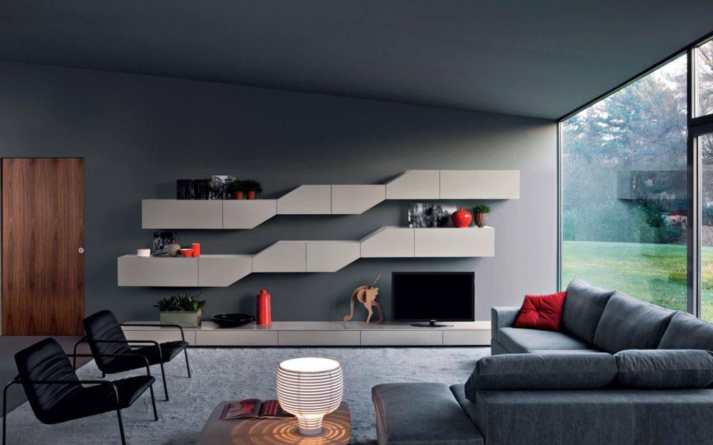 Фото интерьера комнаты с большим угловым диваном серого цвета у окна