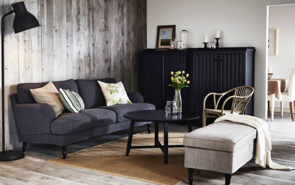 Темно-серый диван в интерьере со светлым пуфиком