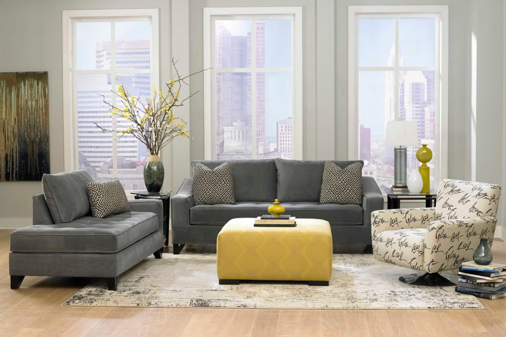 Серый диван и кушетка в интерьере со светлым креслом и желтым пуфиком