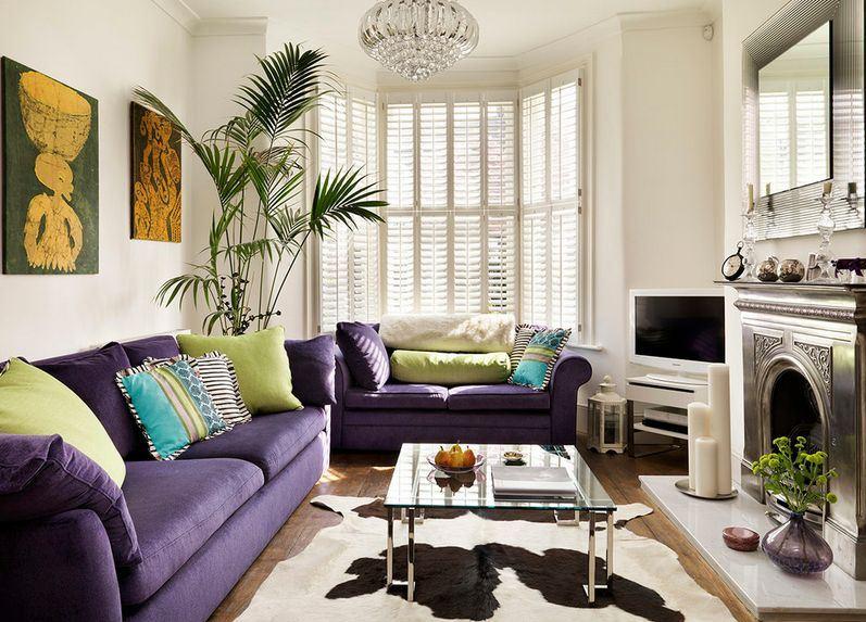 Два фиолетовых дивана в гостиной с камином