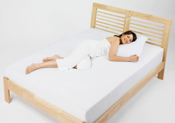 Женщина лежит на кровати с анатомическим матрасом