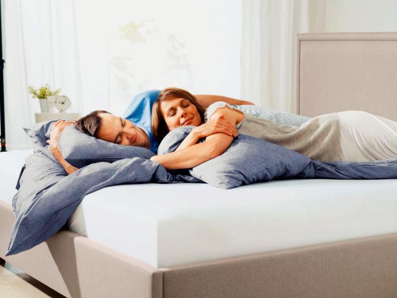 Супружеская пара спит в кровати
