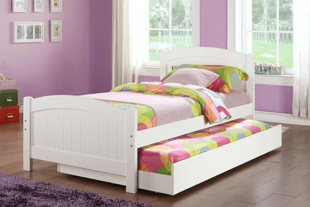 Выкатная кровать посередине детской комнаты с изголовьем и изножьем