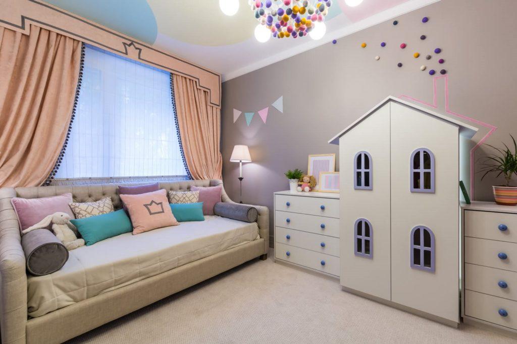 Интерьер детской комнаты с большим прямым диваном для сна у окна