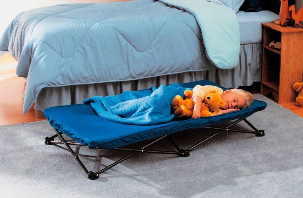 Маленькая девочка спит на раскладушке