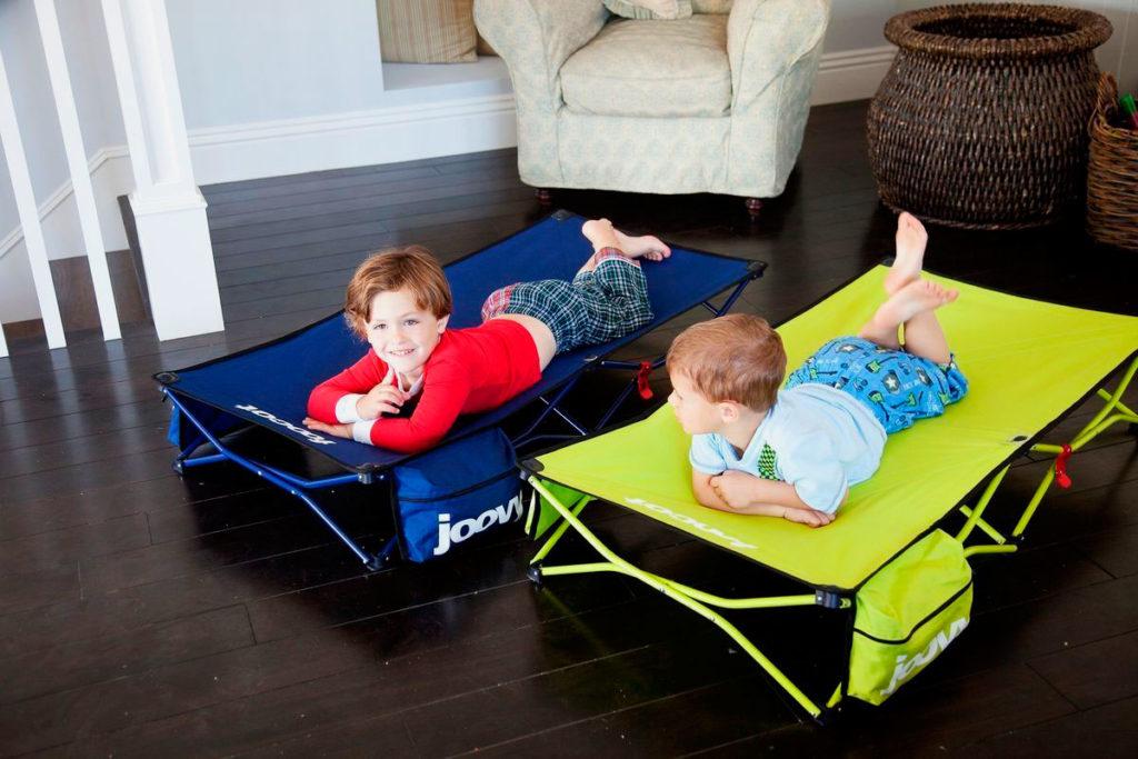 Маленькие дети лежат на раскладушках