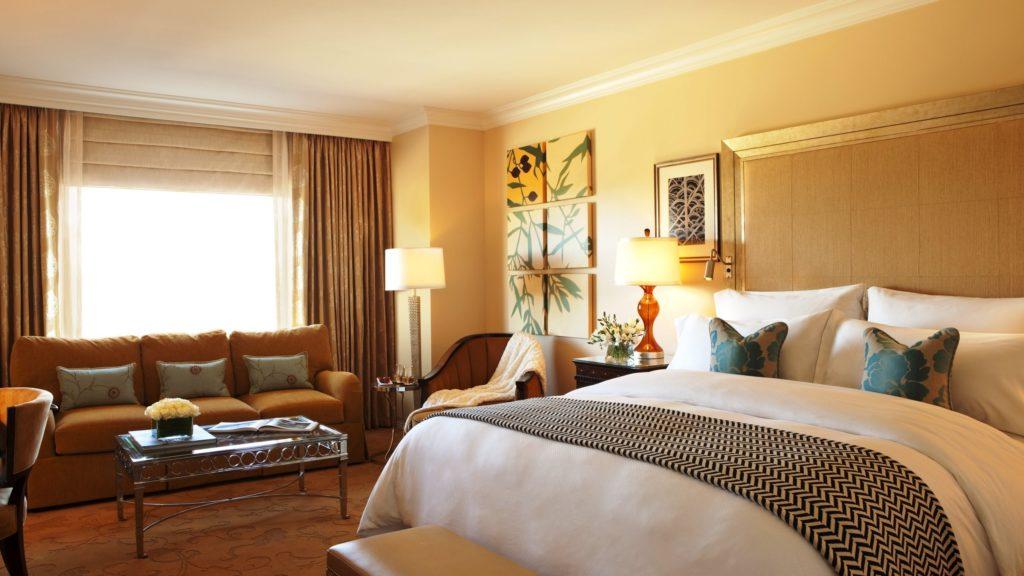 Фото интерьера спальной комнаты с кроватью и небольшим диваном у окна