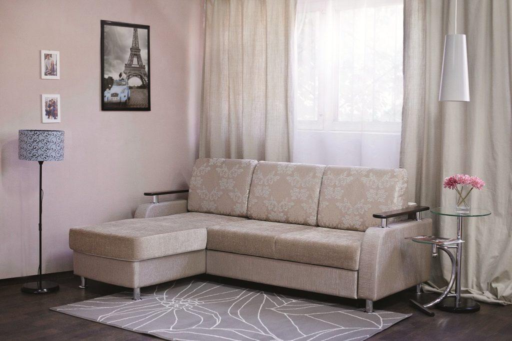 Угловой светло-бежевый диван с узорами в спальной вместо кровати