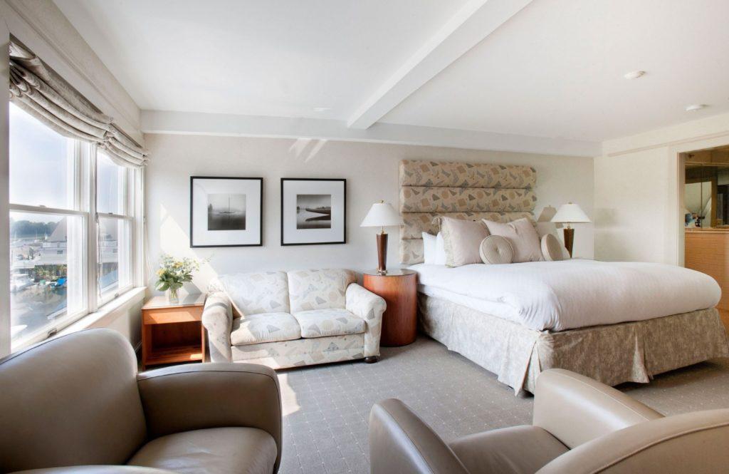 Спальня с большой кроватью и прямым диваном в интерьере
