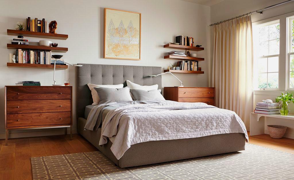 Серая кровать с мягким изголовьем и каркасом в спальной комнате