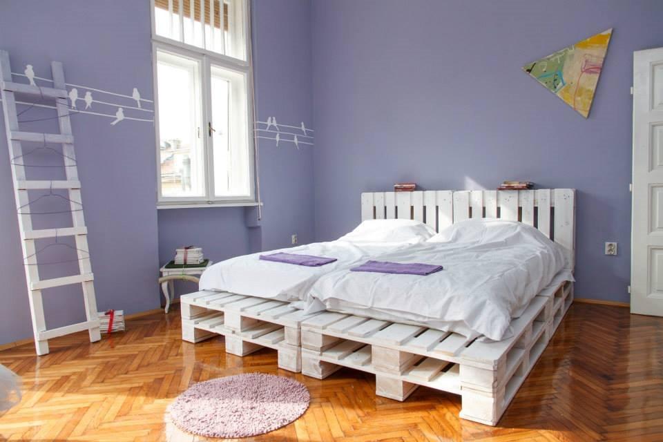 Интерьер спальной с кроватью из паллет окрашенных в белый цвет
