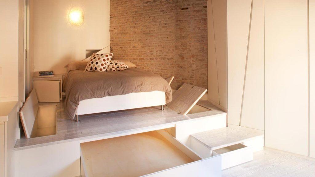 Фото кровати расположенной на подиуме оснащенном встроенными ящиками