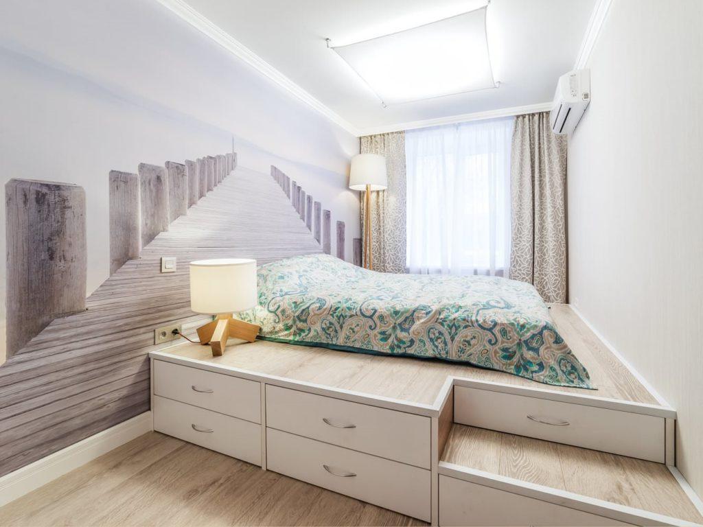 Кровать на подиуме с ящиками в интерьере комнаты