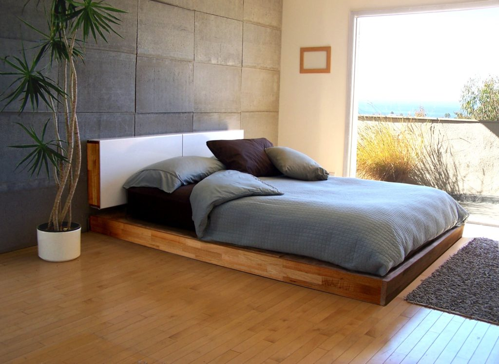 Кровать на низком подиуме в интерьере спальной комнаты