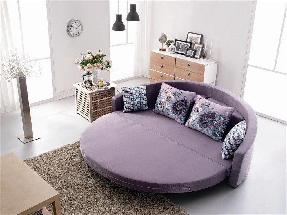 Раскладной круглый диван-кровать со спальным местом в интерьере спальной комнаты