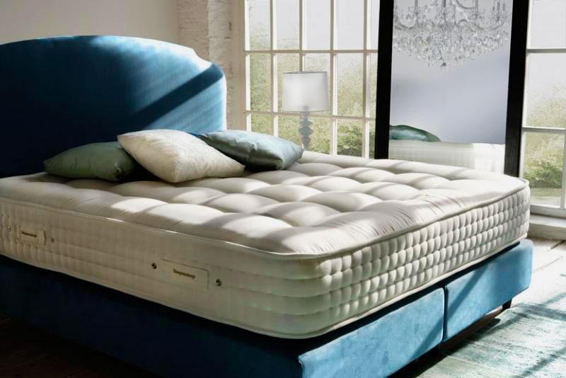 Кровать с большим толстым матрасом в спальной комнате