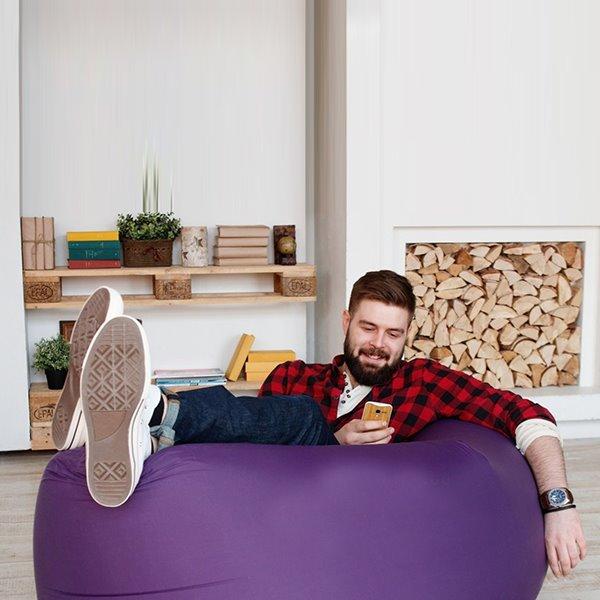 Парень лежит на надувном диване дома