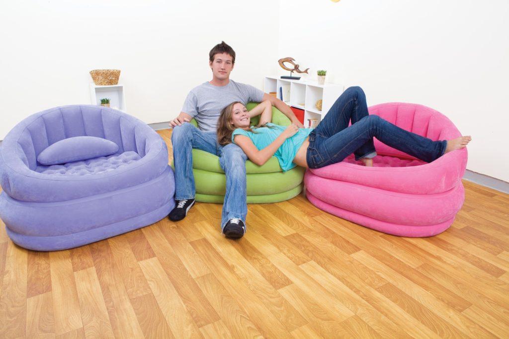 Пара молодых людей сидит на надувных диванах в комнате