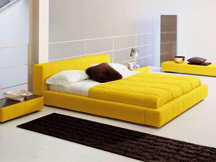 Современный интерьер просторной спальной комнаты с желтой кроватью