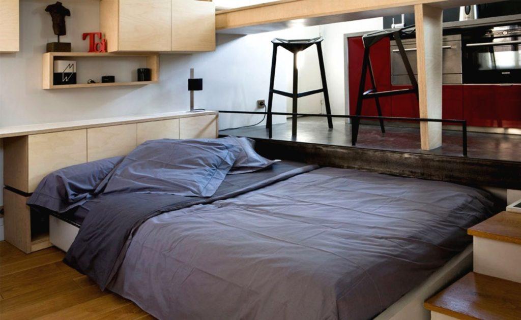 Большая двуспальная кровать под подиумом в интерьере студии