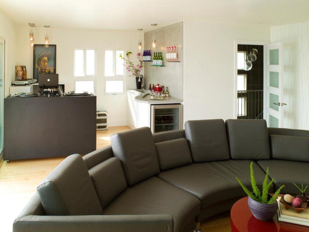 Большой кожаный диван модульного типа в интерьере кухни-гостиной