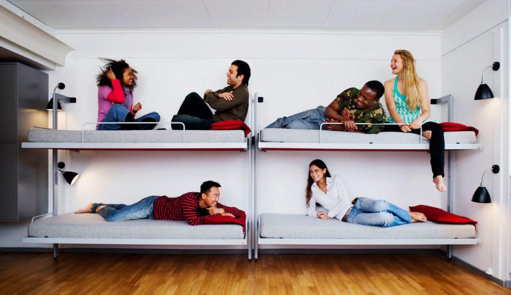Люди общаются сидя на двухъярусных кроватях