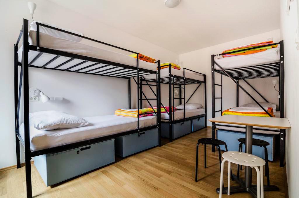Металлические двухъярусные кровати для взрослых в интерьере комнаты