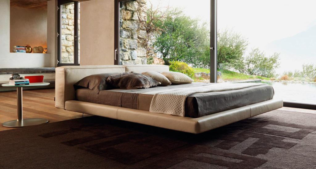 Фото стильной кровати на металлических ножках с кутаным каркасом из кожи