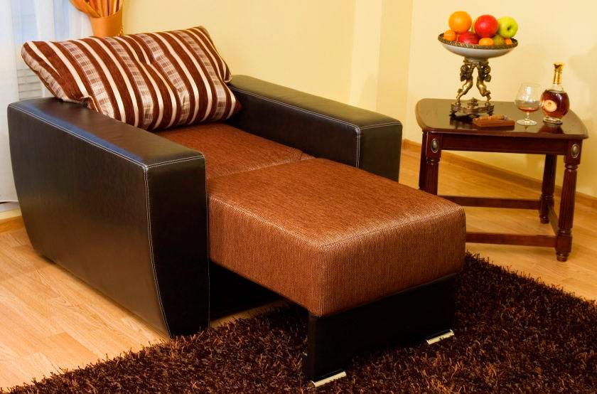 Раскладное кресло-кровать с подлокотниками в интерьере комнаты