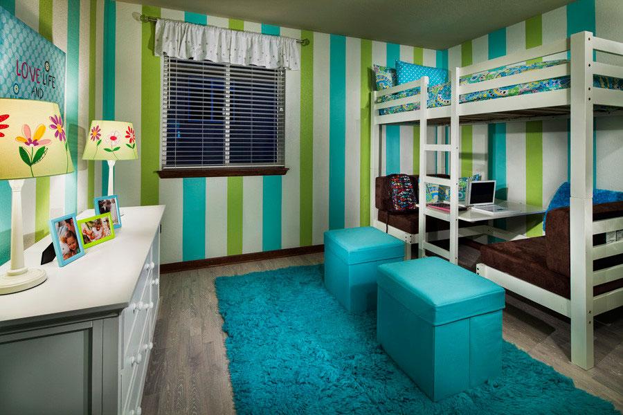 Сдвоенная кровать-чердак с двумя диванами внизу в интерьере комнаты подростков