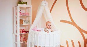 Фото новорожденного ребенка в круглой кроватке с балдахином