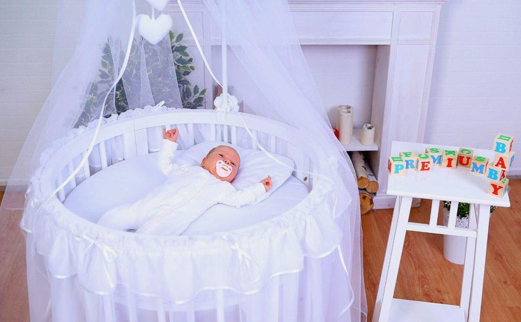 Новорожденный малыш в круглой кроватке