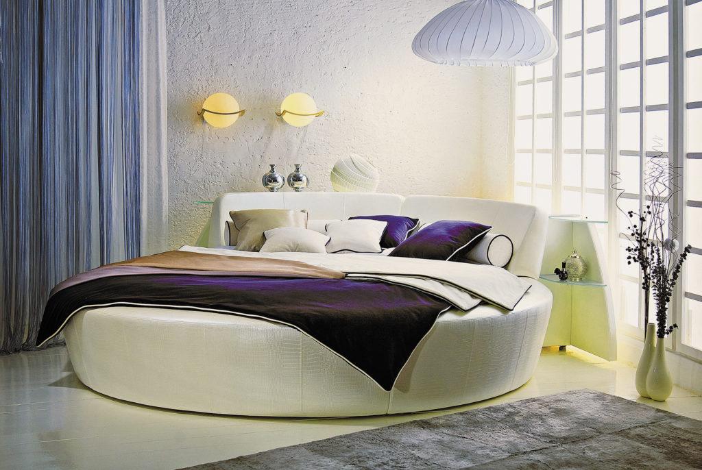 Фото белой круглой кровати с прикроватными столиками в углу комнаты