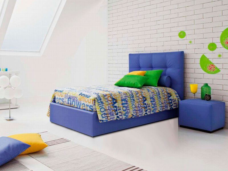 Мягкая синея кровать с большим изголовьем в спальной подростка