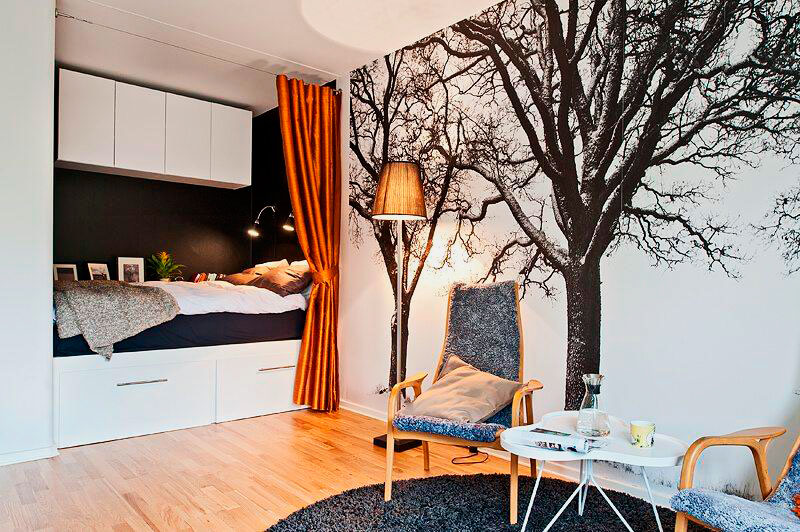 Кровать расположенная в нише комнаты прикрываемая занавесками