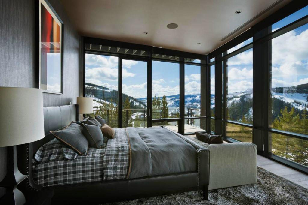 Кровать расположенная напротив панорамных окон