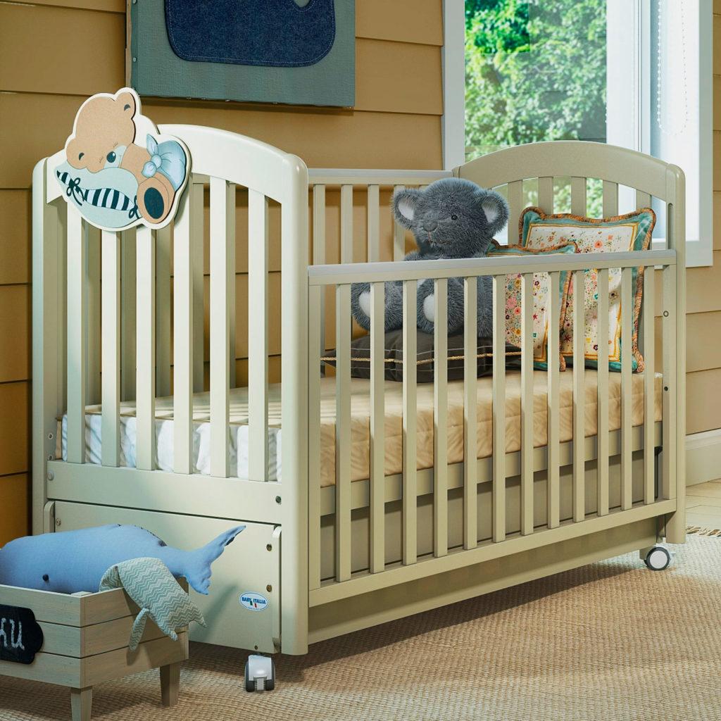 Фото детской кроватки на колесиках с опускаемым бортиком и маятниковым механизмом