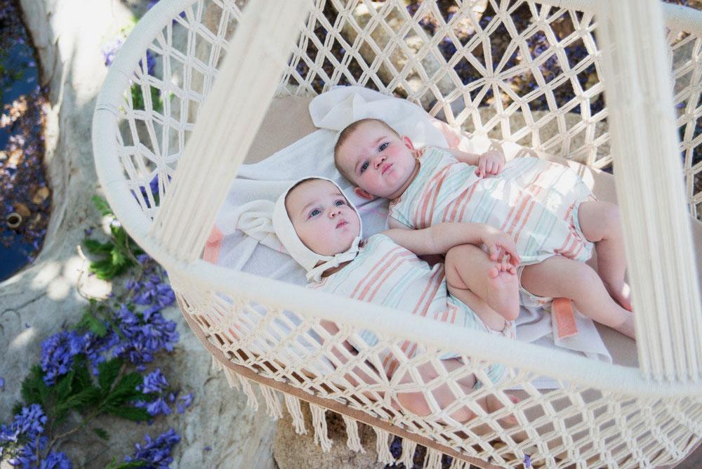 Два младенца в плетенной подвесной колыбели на улице