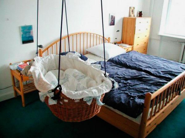Плетенная колыбель подвешенная к потолку рядом с родительской кроватью