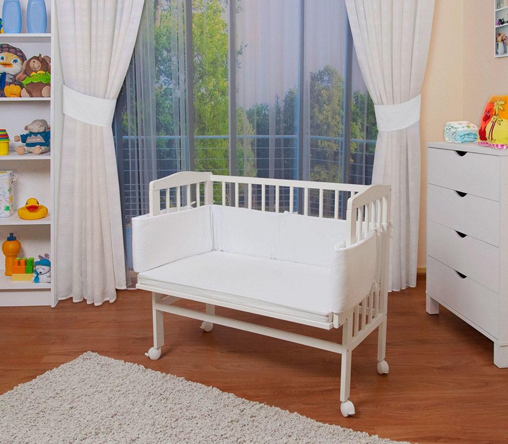 Деревянная кроватка для младенца на колесиках с мягкими накладками на бортиках