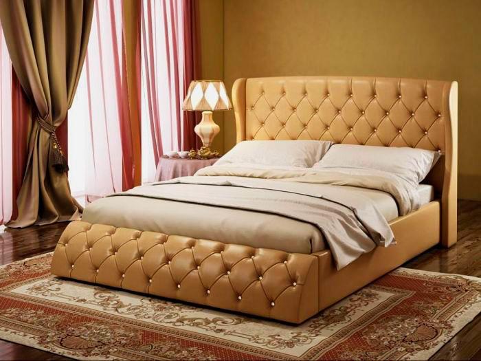 Фото роскошной двуспальной кровати кремового цвета в кожаной отделке с каретным декором